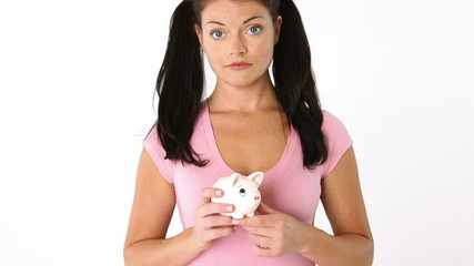 Portrait of young unhappy woman holding a piggy bank