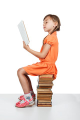 Baby girl sitting on books reading a book