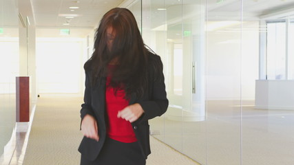 Young businesswoman dancing in office