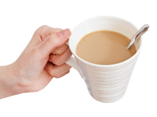 hand holds cup of coffee with milk