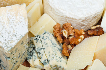 pieces of cheeses on wooden plate