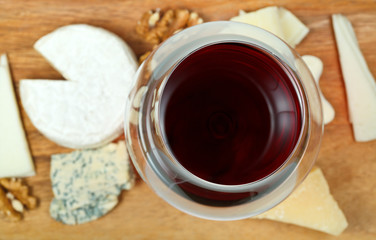 top view of glass of red wine and various cheeses