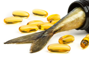 Fish oil capsules and fish tail in brown jar