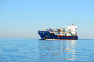 Large cargo container ship sailing in a bright sunny day. Riga,