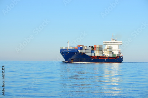 canvas print picture Large cargo container ship sailing in a bright sunny day. Riga,