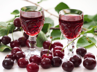 Cherry liqueur in crystal glasses and sour cherries