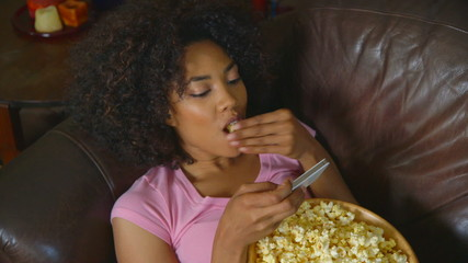 Woman texting and eating popcorn on couch