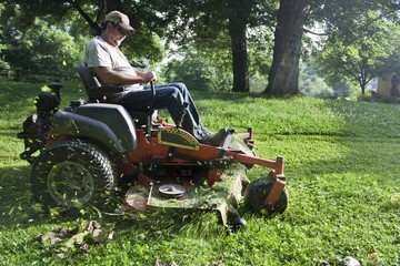 Landscaper cutting grass on riding lawn mower