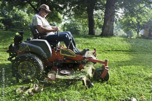 Landscaper cutting grass on riding lawn mower - 66543364