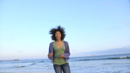 Portrait of woman running and smiling at beach