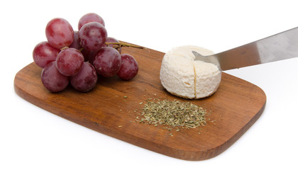 Goat cheese, grapes and provencal herbs on a wooden cutting boar