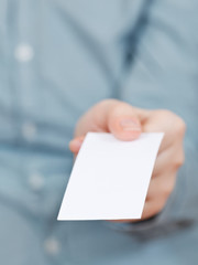 front view of blank business card in fingers