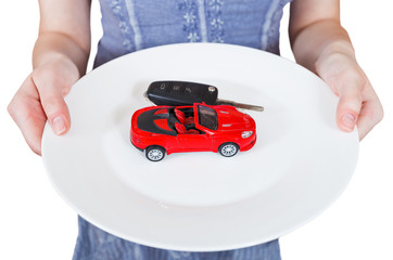 woman holds white plate with new red car