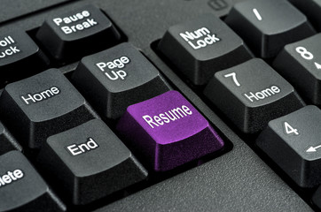 keyboard with the word   resume   written on a button