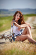 canvas print picture - beautiful smiling girl sitting next to bike, summer time