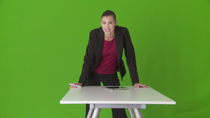 Friendly young businesswoman executive leaning on desk