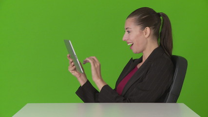 Closeup of young businesswoman at desk using touchscreen and lau