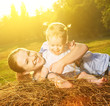 happy family in summer nature. Mother and baby daughter on hay