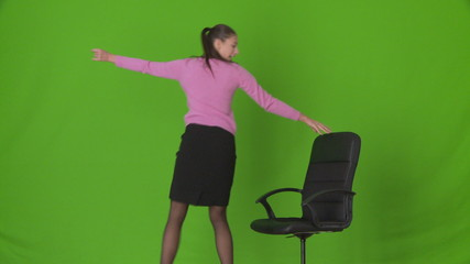 Young businesswoman dancing with office chair
