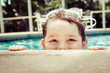 Young child peeking out of pool while swimming in vintage filter