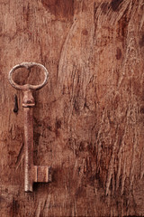 large rusty vintage metal key on old wooden background