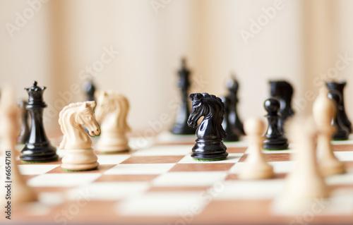 Leinwanddruck Bild Chess pieces set on a chessboard