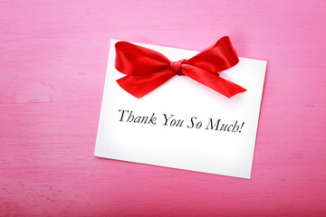 Thank you card on pink wooden board