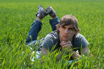 Sexy young man on green grass