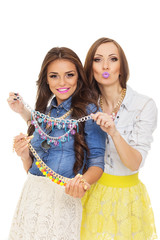 Two fashionable young women choosing a necklace