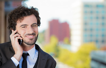 Businessman talking on phone on balcony of his hotel, apartment