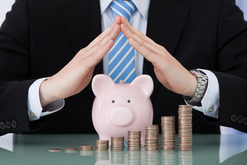 Businessman Sheltering Piggybank And Coin Stacks
