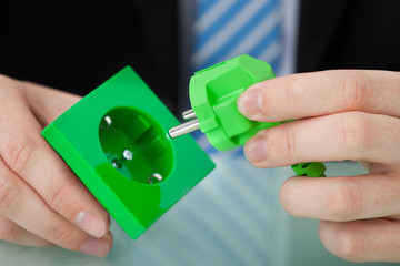 Businessman Holding Green Electric Plug And Socket