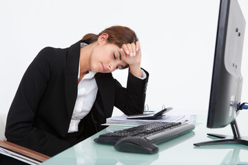 Stressed Businesswoman Leaning At Desk