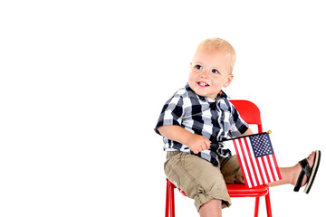 One year old boy holding an American flag sitting