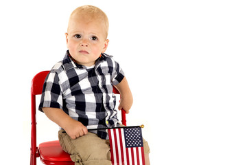 Toddler boy in a red chair holding an American flag