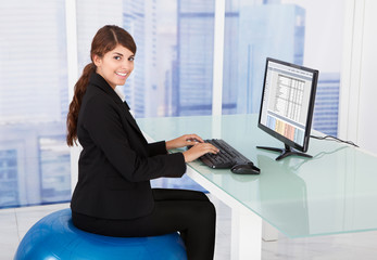 Businesswoman Using Computer While Sitting On Fitness Ball