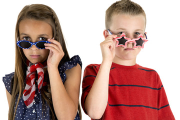 cute girl and boy peering over American patriotic glasses