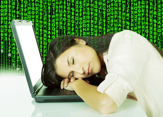 Young Woman Sleeping On Laptop At Desk