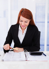 Businesswoman Examining Documents With Magnifying Glass
