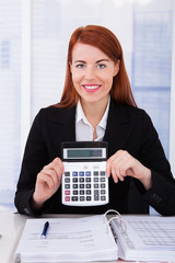 Happy Businesswoman Holding Calculator At Office Desk
