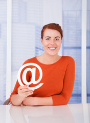 Beautiful Woman Holding Internet Symbol At Desk