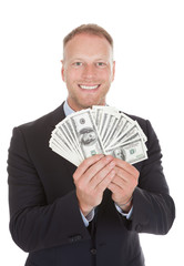 Smiling Businessman Holding Bank Notes