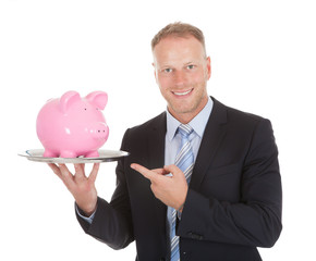 Businessman Showing Piggybank On Tray