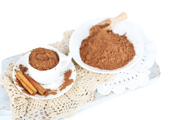 Cocoa powder in cup on napkin on wooden board isolated on white