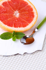 Half of grapefruit and spoon on wooden board on light
