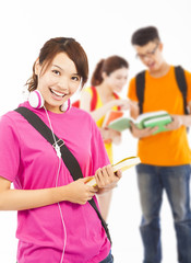 smiling young student holding books and earphone with classmates