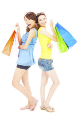 happy young sisters standing and holding shopping bags