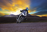 young man riding motorcycle in asphalt road curve with rural and