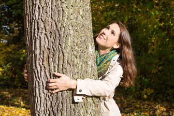 Herbst: Frau im Wald umarmt einen Baum und ist glücklich
