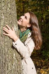 Frau im Herbst umarmt einen Baum